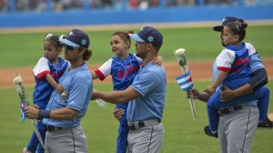 Members of the Tampa Bay Rays carry children and flowers before an exhibition baseball game between the Tampa Bay Rays and the Cuban National team at the Estadio Latinoamericano, Tuesday, March 22, 2016, in Havana, Cuba, that President Barack Obama and Cuban President Raul Castro attended. (AP Photo/Pablo Martinez Monsivais)